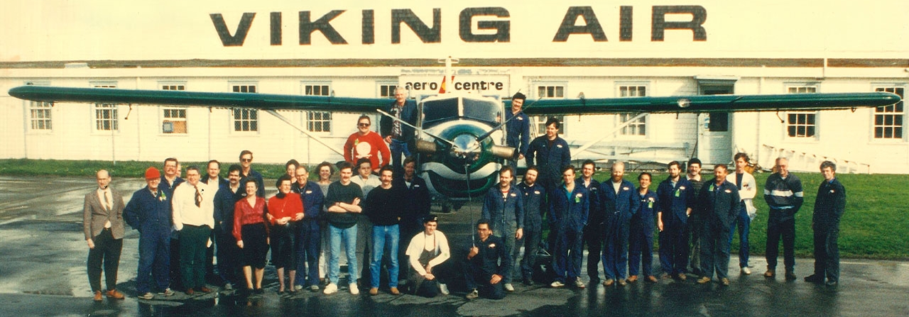 A group of Viking employees stand in front of an aircraft.