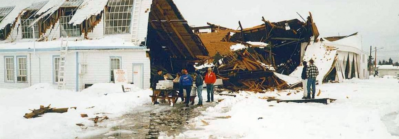 A DHC-2 Turbo Beaver is crushed under a collapsed hangar.